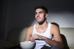 Young man eating popcorn and watching movies Kuvituskuvat