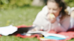Blurred background of female student studying outdoors in a park on a bright day Stock Footage