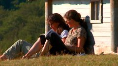 Young women reading a book next to the huts in the ethno village Stock Footage