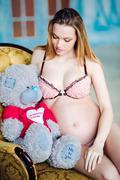 Beautiful pregnant woman in sexy nightwear sitting on armchair with teddy bear Stock Photos