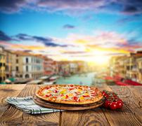Rustic pizza with old city Italy background - stock photo