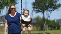 Mom swinging her toddler at the playground Stock Footage