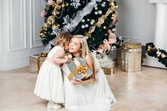 Happy family mother and daughter at  New Year with gifts around the Christmas Stock Photos