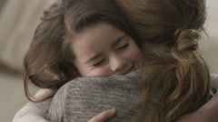 Daughter rushes into mother's arms at home and gives her a big hug. - stock footage