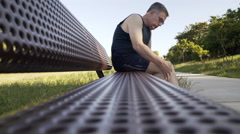 middle age man with knee pain on a park bench 4k - stock footage