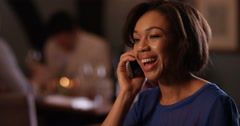 4K Close up portrait of young woman on her own, talking on phone in bar at night Stock Footage