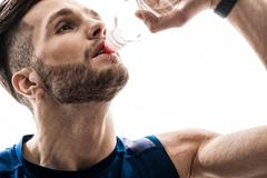 Cheerful thirsty sportsman drinking water from bottle - stock photo