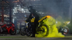 Super sport motorcycle doing a tire burnout with colorful sand, holi. Stock Footage