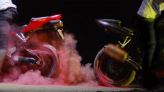 Super sport motorcycles doing a tire burnout with colorful sand, holi. Stock Footage