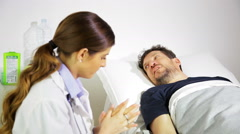 Patient lying in bed talking to doctor in hospital Stock Footage
