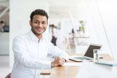Cheerful Arabian businessman is doing his work Stock Photos