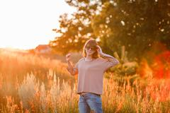 young modern girl on background sunset. - stock photo