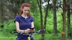 Girl sitting on the bike and texting on smartphone Stock Footage