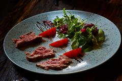Grilled sliced roast beef and green salad - stock photo