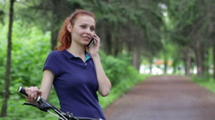 Young woman on bike in park talking on cell phone Stock Footage