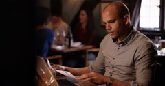 4K Worried restaurant owner working on laptop & looking over business figures Stock Footage