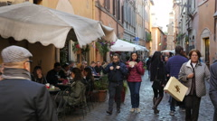 People walk rest eat and drink in cozy cafes and restaurants of Rome Italy Stock Footage