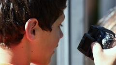 A boy looking at photos on a camera Stock Footage