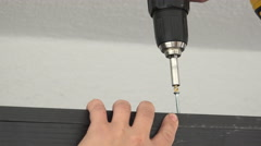 Craftsman drives the screw into furniture cabinet board with an electric powe - stock footage