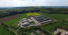 Solar and Biogas power plants from above with wind turbines in background. Stock Footage