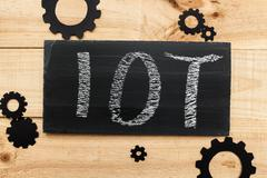 IOT letters in a blackboard on a dark wooden background - stock photo