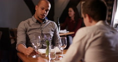 4K Relationship problems, gay male couple having intense conversation in bar or  Stock Footage