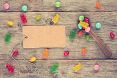 Blank tag and spoon with candies - stock photo