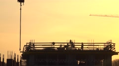 Silhouettes of construction workers against orange sky. 4K telephoto lens shot Stock Footage