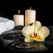spa background of yellow orchid (phalaenopsis) on zen stones, drops, candles  - stock photo