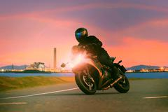 Young man riding sport touring motorcycle on asphalt highways against beautif Stock Photos