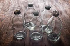 Top view of dirty empty vintage transparent glass bottles with stopper on woo Stock Photos