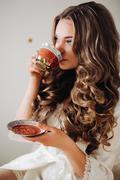 Sexy bride in a white robe drinking tea. Wavy hair, wound, makeup bright wedding Stock Photos