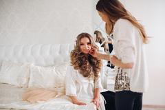Bride doing makeup in the morning in a room. make-up artist doing professional Stock Photos