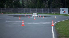 White car is driving between traffic cones Stock Footage