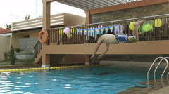 Man dives into the pool. High-delayed and slow motion jump shot. Stock Footage