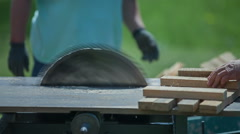 Cutting wood and putting it into a wheelbarrow Stock Footage
