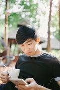 A man drinking morning coffee in sunshine light reading good news on mobile p - stock photo