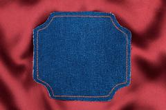 Frame made of denim fabric with yellow stitch on red silk  with space for you Stock Photos