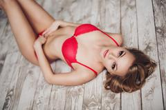 Sexy young woman in red lingerie lying on the floor Stock Photos