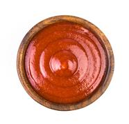 Wood bowl of ketchup isolated on white background. Top view Stock Photos