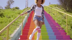 Young Woman Walks Down The Colorful Stairs. Stock Footage