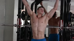 Athlete doing exercises for the ABS on the horizontal bar in the gym - stock footage