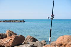 Fishing pole with red reel on blue sea - stock photo