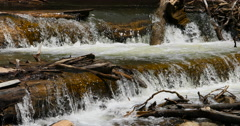 High mountain creek waterfall over fallen trees DCI 4K Stock Footage