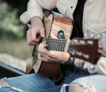 Man hands on the guitar strings close up image Stock Photos