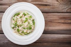 Homemade risotto with chicken, green peas, arugula and parmesan - stock photo