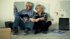 Mature couple with tablet on floor fighting about new home project  Stock Footage