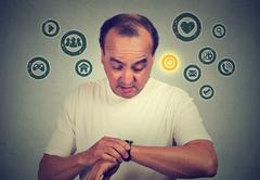 Middle age man using checking time on his smart watch with apps icons on gray Stock Photos