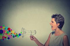 angry screaming young woman with megaphone - stock photo