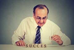 Successful businessman arranging wooden cubes reading success. Stock Photos